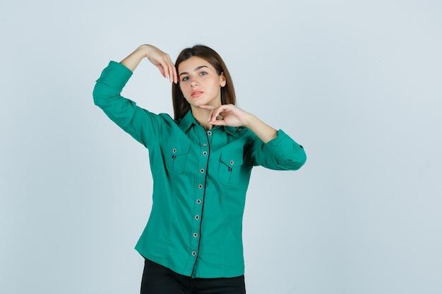 Молодая женщина в зеленой рубашке позирует с руками вокруг головы и выглядит деликатно, вид спереди.