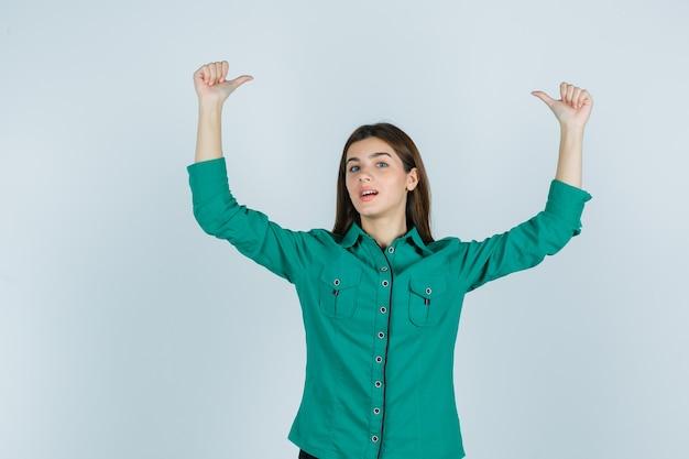 緑のシャツを着た若い女性は、二重の親指を上に示し、自信を持って、正面図を示しています。