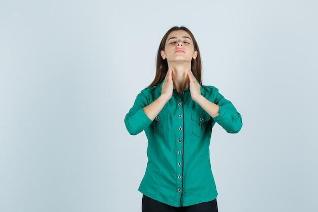 Молодая женщина в зеленой рубашке трогает кожу на шее и выглядит расслабленной, вид спереди.