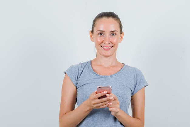Молодая женщина в серой футболке держит мобильный телефон и выглядит веселым, вид спереди.