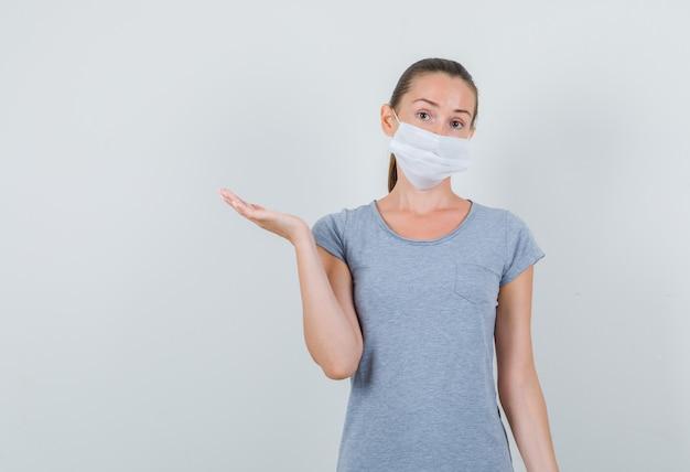 灰色のtシャツ、開いた手のひらを上げるマスク、正面図の若い女性。