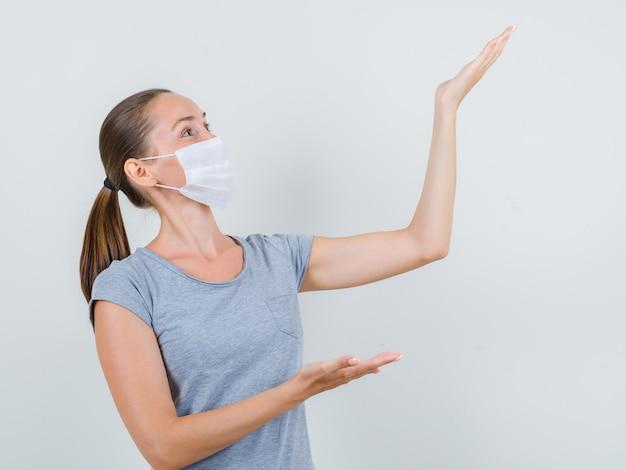 Молодая женщина в серой футболке, маска показывает или поднимает что-то и выглядит веселым, вид спереди.