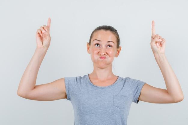 上向きと頬を吹く灰色のtシャツの若い女性、正面図。
