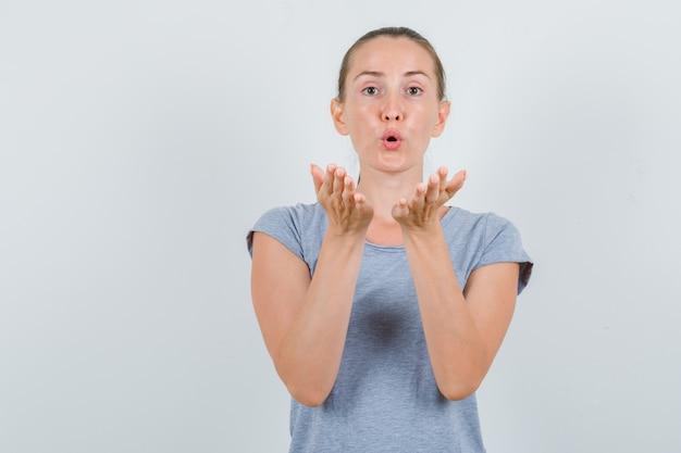 空気のキスを送信する灰色のtシャツの若い女性、正面図。