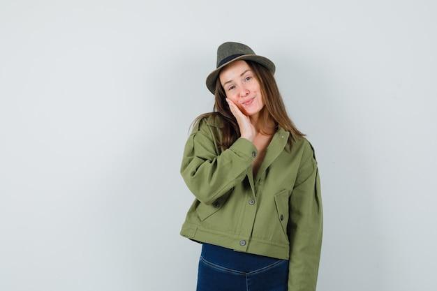 재킷, 바지, 손바닥에 뺨을 기울고 귀여운, 전면보기를 찾고 모자 젊은 여성.