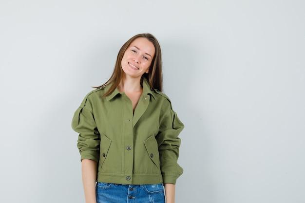 ジャケット、ショートパンツ、魅力的に見える若い女性。正面図。