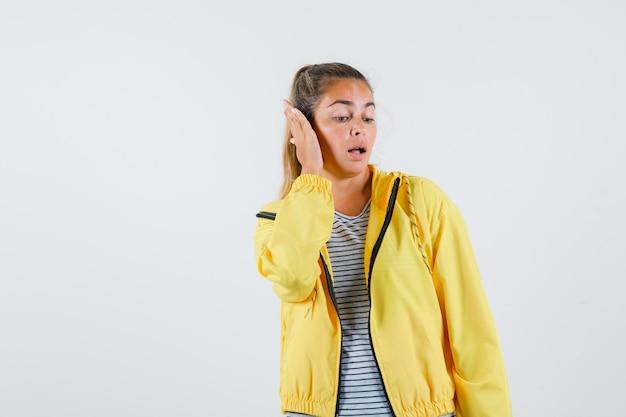 Молодая женщина в куртке, футболке держит руку на ухе и выглядит красиво, вид спереди.