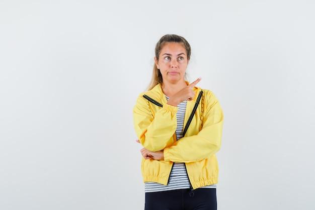 ジャケットを着た若い女性、右上隅を指して物思いにふけるtシャツ、正面図。