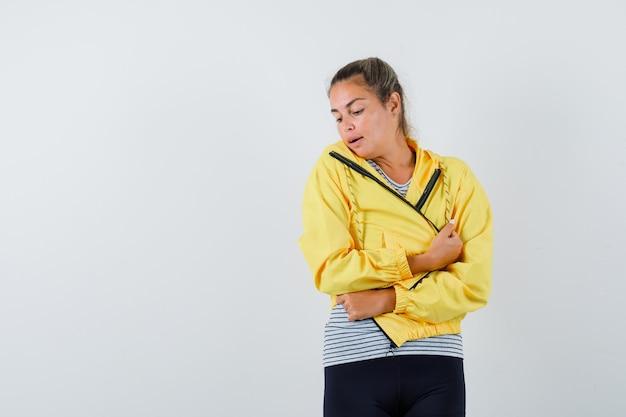 ジャケットを着た若い女性、立って魅力的に見ながらポーズをとるtシャツ、正面図。