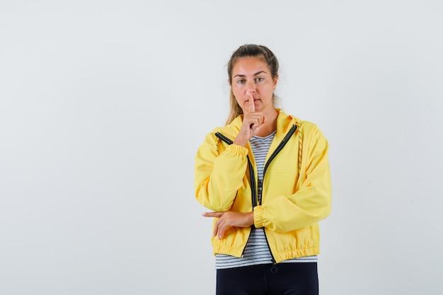 ジャケットを着た若い女性、沈黙のジェスチャーを示し、自信を持って見えるtシャツ、正面図。
