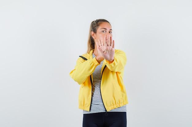 ジャケットを着た若い女性、停止ジェスチャーを示し、自信を持って見えるtシャツ、正面図。