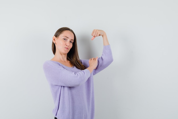彼女の腕の筋肉を示し、強力に見えるライラックブラウスの若い女性