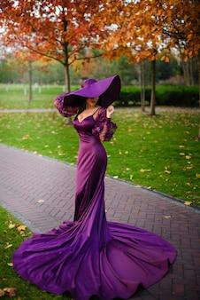 Молодая женщина в роскошном платье стоит в осеннем парке