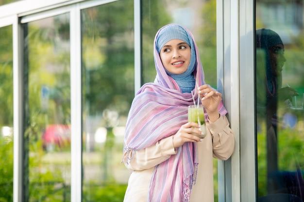 イスラム教徒のヒジャーブ屋外の窓のそばに立って、寒さの中にさわやかなドリンクを飲んでいる若い女性