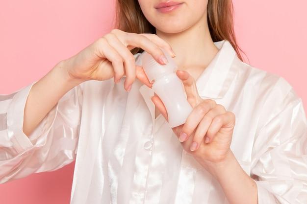 Молодая женщина в пижаме и маске для сна держит банку на розовом