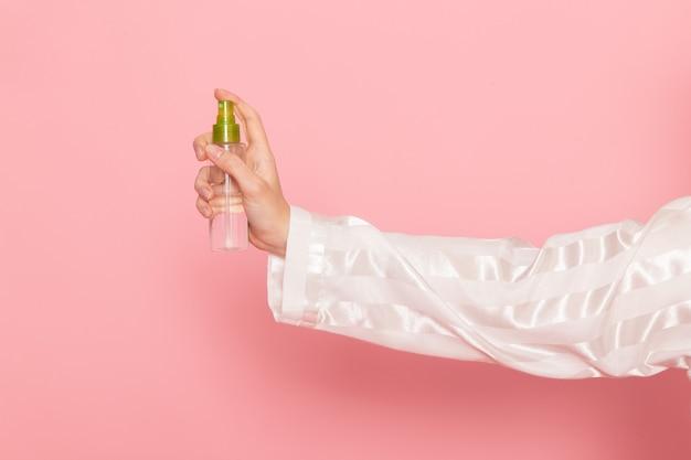 Молодая женщина в пижаме и маске для сна держит спрей для макияжа на розовом
