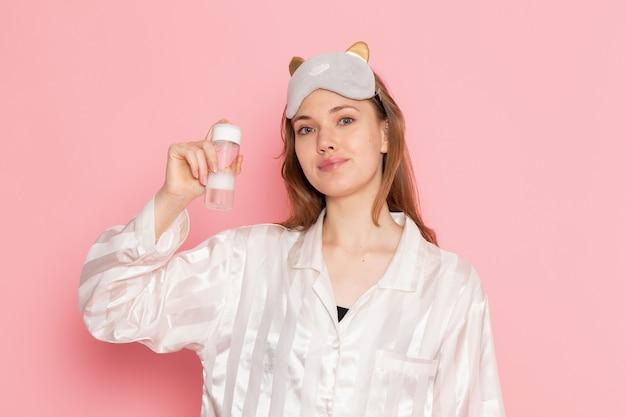 Молодая женщина в пижаме и маске для сна держит баллончик с улыбкой на розовом