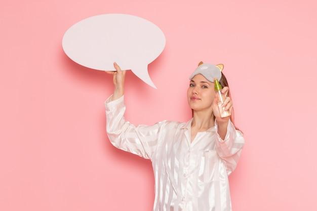 Молодая женщина в пижаме и маске для сна держит белый знак спрей на розовом
