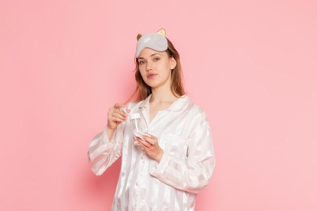 Молодая женщина в пижаме и маске для сна позирует и держит спрей для макияжа на розовом