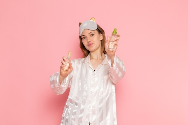 パジャマと睡眠マスクのポーズとピンクのメイクアップスプレーを保持している若い女性