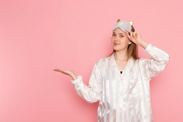 Молодая женщина в пижаме и маске для сна позирует, улыбаясь на розовом