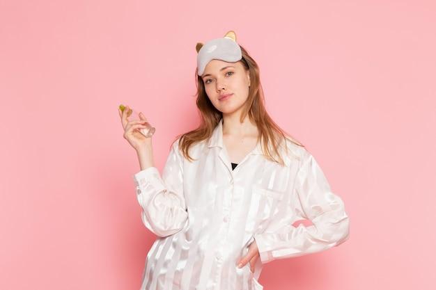 パジャマとスリープマスクのメイクアップスプレーを使用して、ピンクのポーズで若い女性