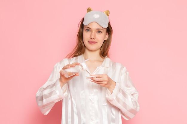 パジャマとメイクアップスプレーを使用してピンクに笑みを浮かべて睡眠マスクの若い女性