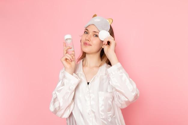 ピンクの笑顔でメイクアップスプレーを使用してパジャマと睡眠マスクの若い女性