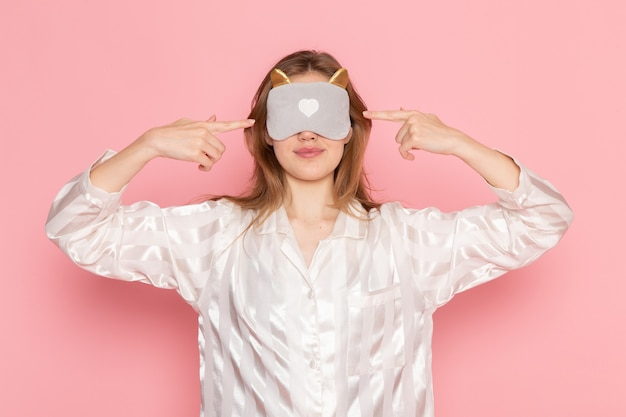 Молодая женщина в пижаме и маске для сна с закрытыми глазами на розовом