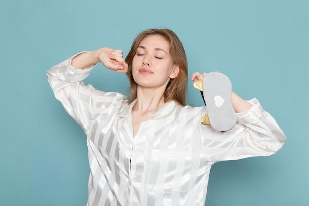 パジャマと睡眠マスクのあくびと青でポーズの若い女性