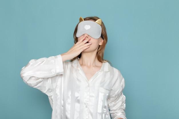 Молодая женщина в пижаме и маске для сна, зевая на синем