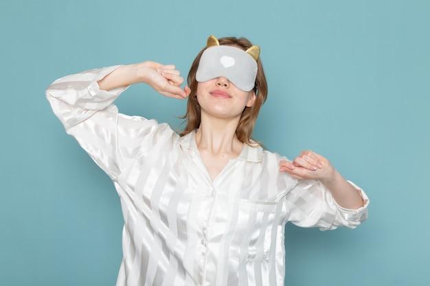 잠옷과 수면 마스크를 입은 젊은 여성이 파란색으로 하품