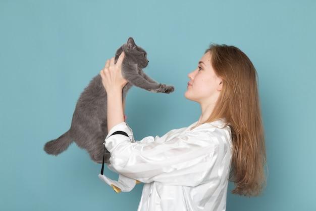 青にかわいい灰色の子猫を保持しているパジャマの若い女性