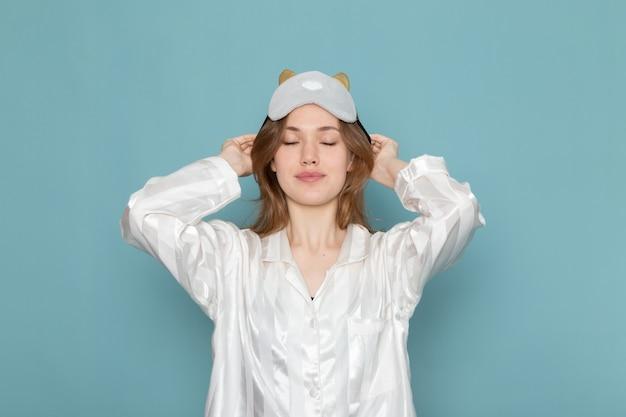 Молодая женщина в пижаме снимает маску для сна на синем