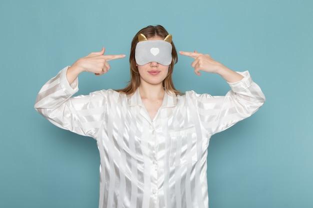青の睡眠マスクを着ているパジャマの若い女性