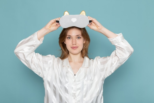 Молодая женщина в пижаме в маске для сна на синем