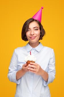 黄色の背景に誕生日のお祝いの間にキャンドルとカップケーキを楽しみながら笑顔とカメラを見ているパーティーハットの若い女性