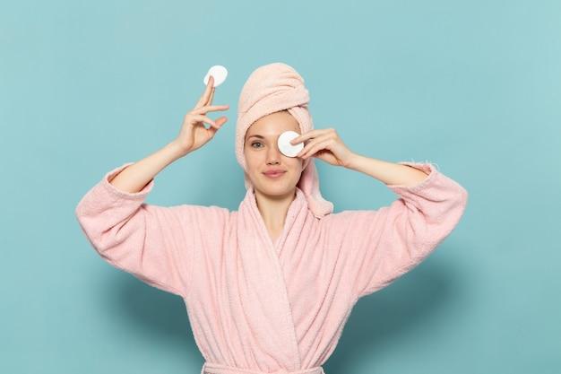 Молодая женщина в розовом халате после душа очищает макияж на синем