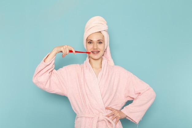 Молодая женщина в розовом халате после душа чистит зубы на синем