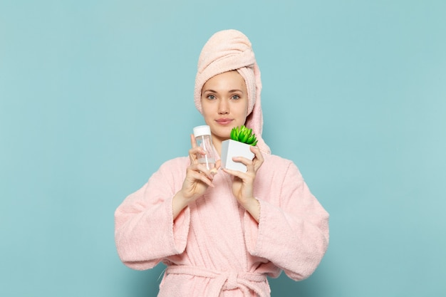 Молодая женщина в розовом халате после душа держит маленькое растение и брызгает на синий