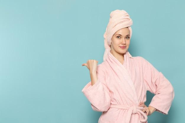 ちょうど青いポーズシャワーの後ピンクのバスローブの若い女性