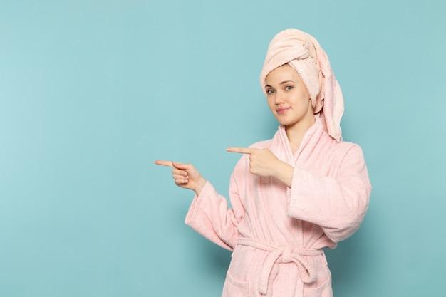 Молодая женщина в розовом халате после душа позирует с улыбкой на синем