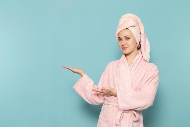 Молодая женщина в розовом халате после душа улыбается и позирует на синем