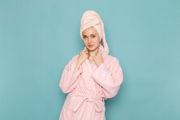 シャワーの笑顔とブルーでポーズした後ピンクのバスローブの若い女性