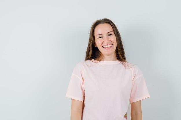 ピンクのtシャツを着た若い女性と陽気に見える、正面図。