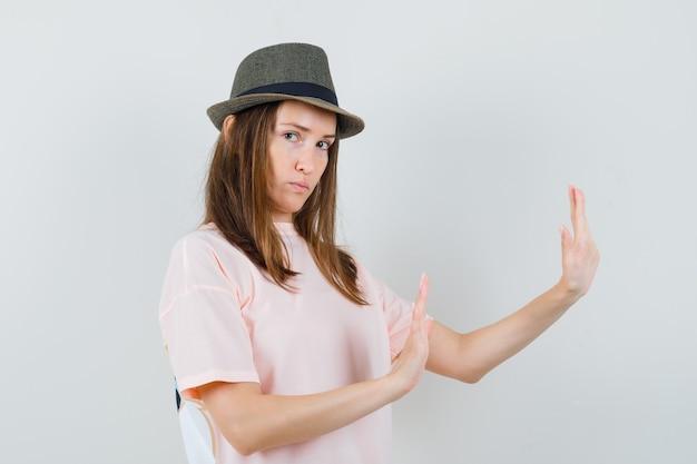 분홍색 티셔츠에 젊은 여성, 모자를 손에 들고 자신을 방어하고 엄격한 전면보기를 찾고 있습니다.