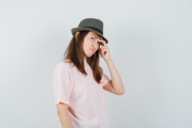 ピンクのtシャツを着た若い女性、帽子がこめかみをこすり、悲しそうに見える、正面図。