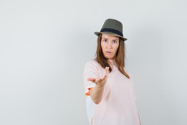 ピンクのtシャツ、困惑したジェスチャーで手を伸ばす帽子、正面図の若い女性。