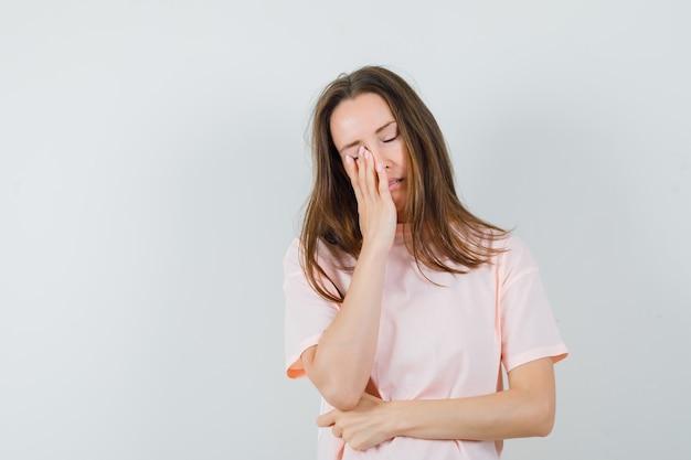 顔に手をつないで、疲れ果てているように見えるピンクのtシャツの若い女性、正面図。
