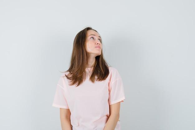 ピンクのtシャツを着た若い女性が上向きに見え、焦点を合わせて、正面図。